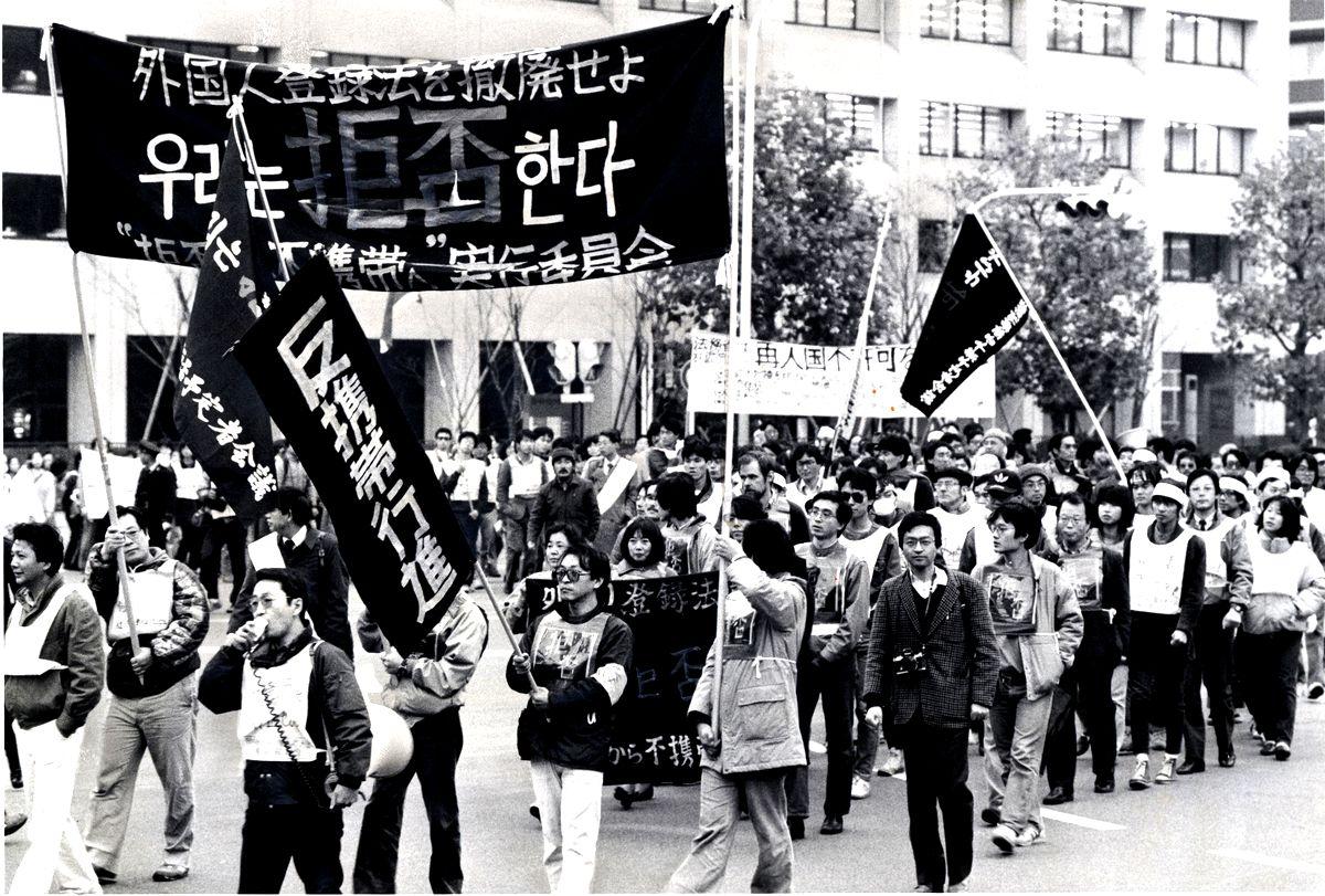 写真・図版 : 指紋押捺廃止に加え、外国人登録証の常時携帯義務廃止も求めてデモ行進する人たち=1985年12月、東京・外務省前