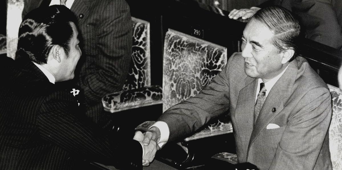 写真・図版 : 国鉄改革法が成立した衆院本会議場で橋本龍太郎運輸相と握手する中曽根康弘首相=1986年11月28日