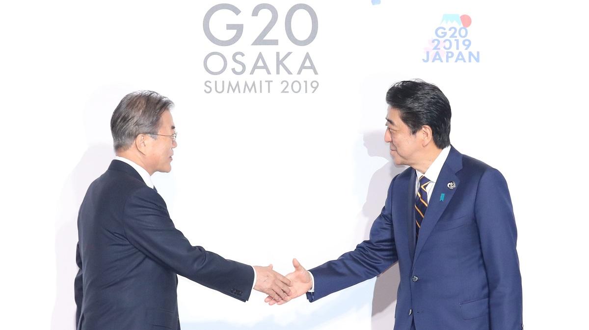 写真・図版 : 大阪で開かれたG20で、韓国の文在寅大統領(左)を出迎える安倍晋三首相=2019年6月28日