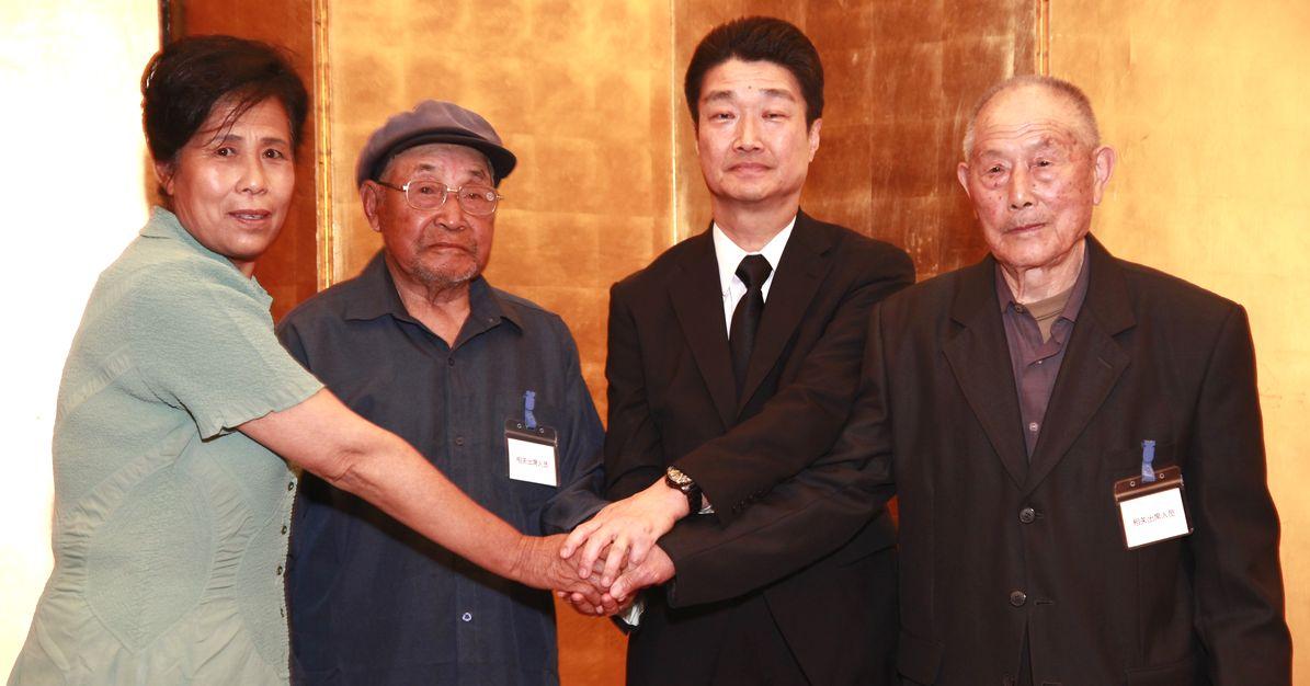 写真・図版 : 強制連行の和解合意書調印式で三菱マテリアル幹部(右から2人目)と手を握り合う中国人元労働者や遺族=2016年6月1日、北京