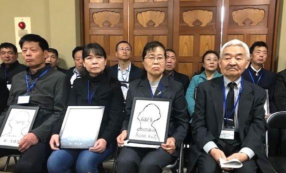 写真・図版 : 花岡事件など強制連行の犠牲者らを慰霊する日中合同法要が2019年11月18日、東京都江東区で営まれた。遺影代わりの額を持つ遺家族と一緒に田中宏さん(右)も最前列に座った=筆者撮影