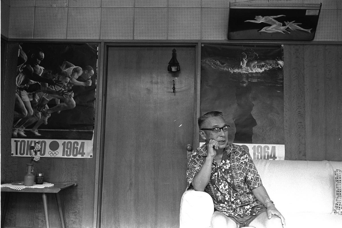 写真・図版 : 東京五輪のポスターが貼られた自宅応接間に座る田畑政治=1963年「アサヒグラフ」掲載の写真