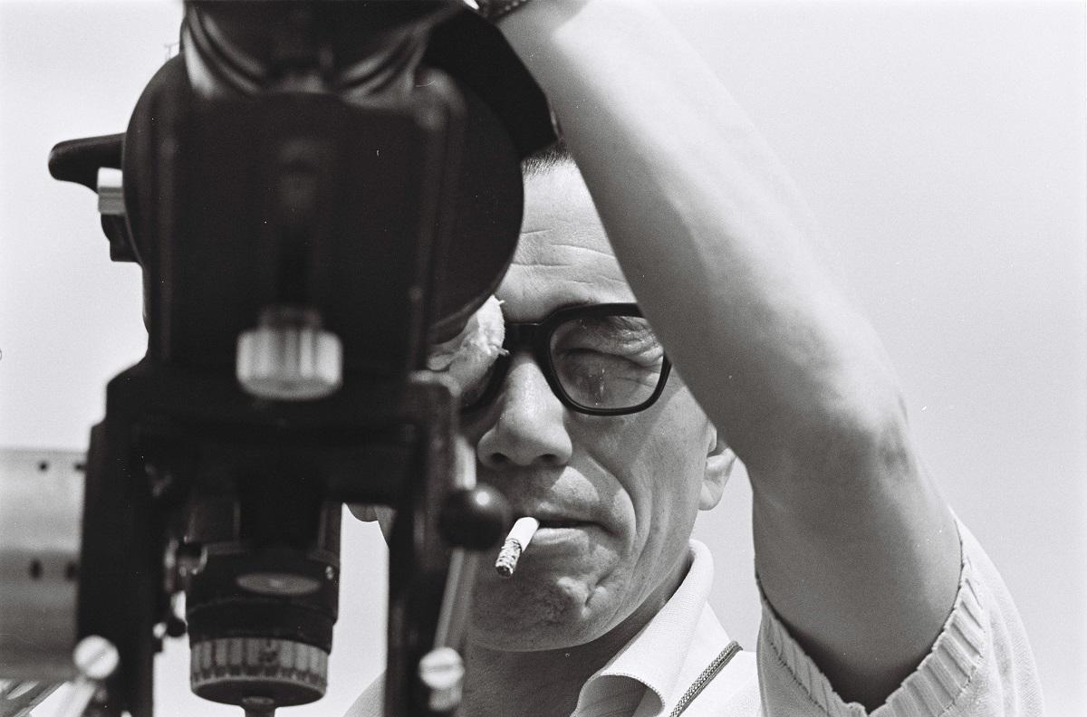 写真・図版 : 1964年東京オリンピックの記録映画を監督した市川崑。自らファインダーをのぞく。完成した作品は大ヒットしたが「記録か芸術か」の議論も巻き起こした