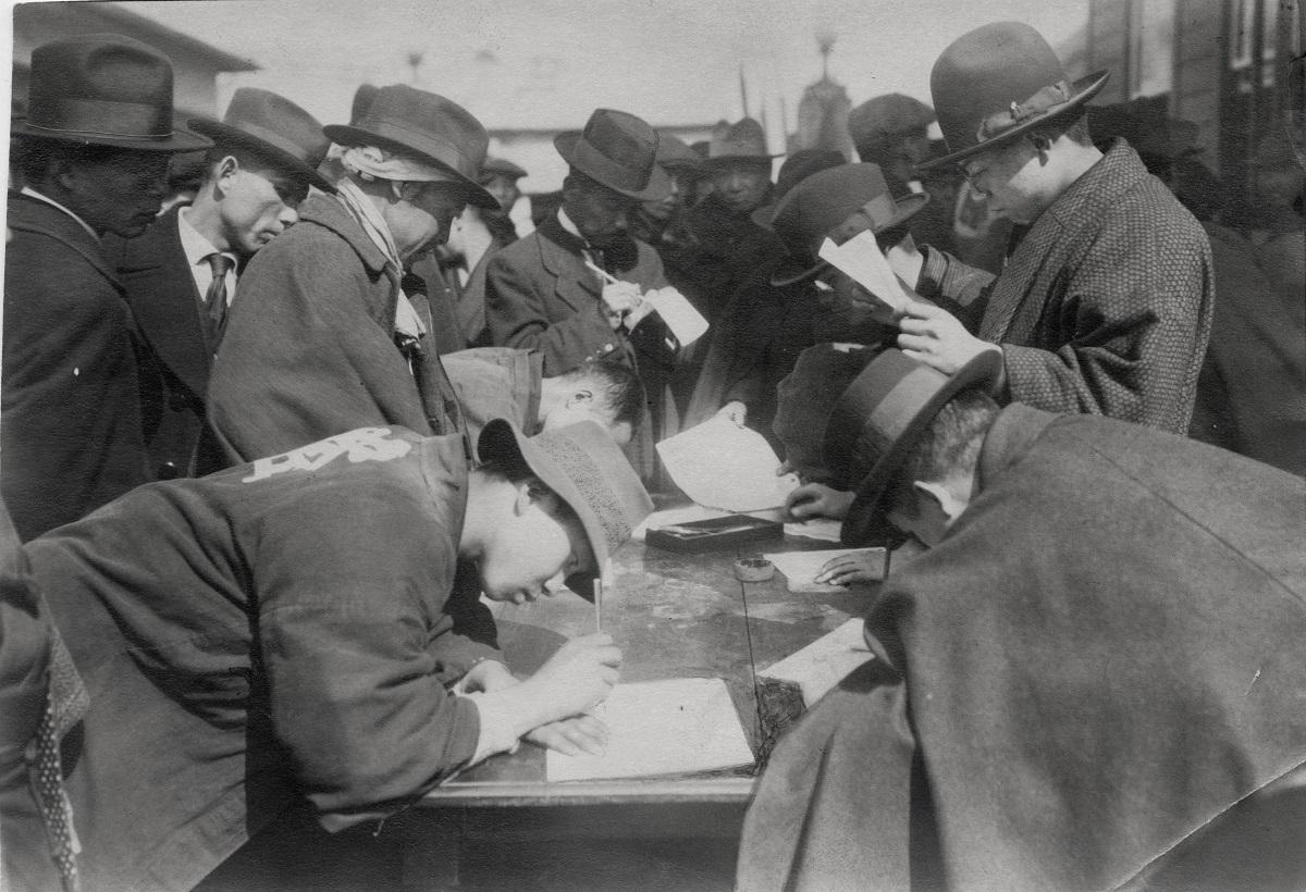 写真・図版 : 1922年2月23日は「普選請願デー」とされ、多くの人々が普通選挙法の成立を求める国会への請願書に署名した=東京・西新橋にあった憲政会本部前
