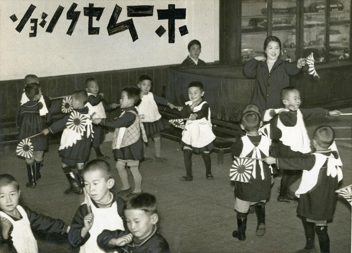 写真・図版 : 戦争遊戯「軍艦マーチ」を披露する、大阪・江戸堀幼稚園の園児たち=1937年11月