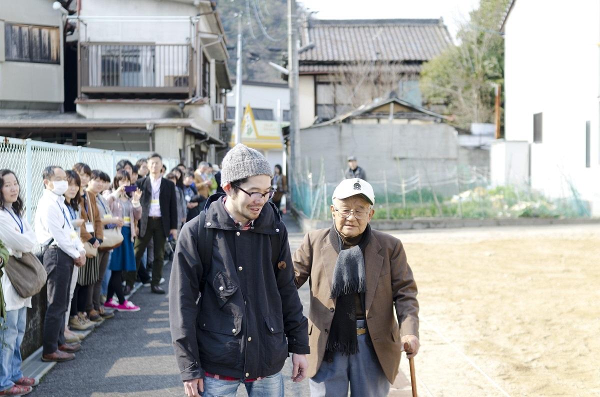 写真・図版 : 『よみちにひはくれない』の上演で、岡田忠雄さん(右)と筆者が街を歩く