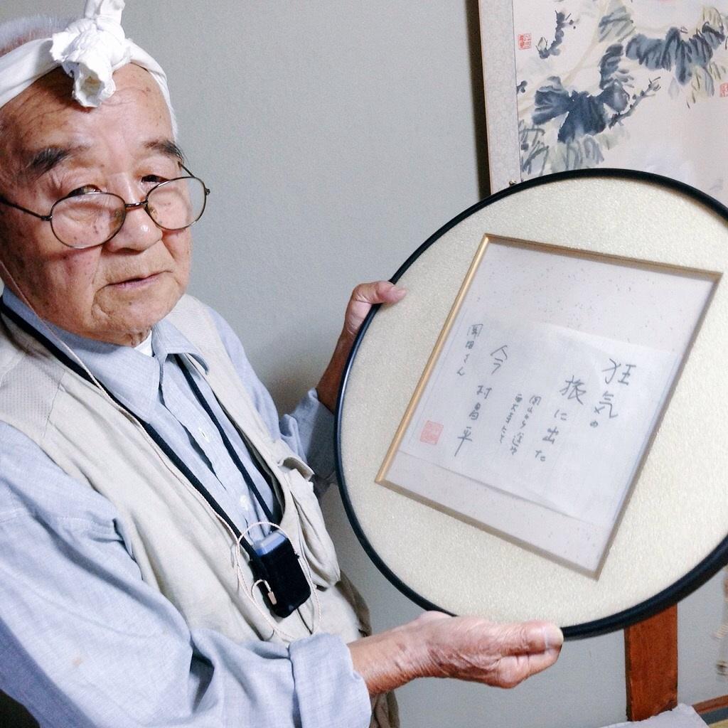 写真・図版 : 今村昌平監督の色紙を手にする岡田忠雄さん