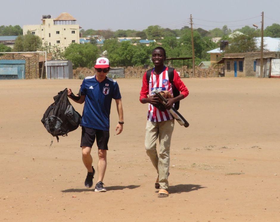 写真・図版 : 持ち帰った貸し出し野球道具を持ってきた大荷物のジオン君(右)を助けるダイス。