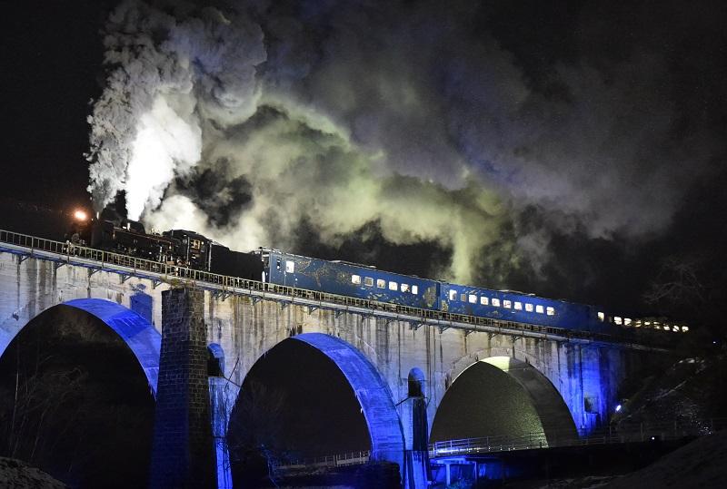 写真・図版 : ライトアップされた「めがね橋」を走る特別運行の「SL銀河」=2014年12月6日、岩手県遠野市、福留庸友撮影