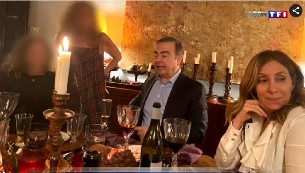写真・図版 : 仏テレビ局TF1が入手した、日産自動車前会長のカルロス・ゴーン被告(中央)の写真。大晦日にベイルート市内で妻のキャロル氏(右)と新年を祝う宴を開いている様子だという=TF1の映像から