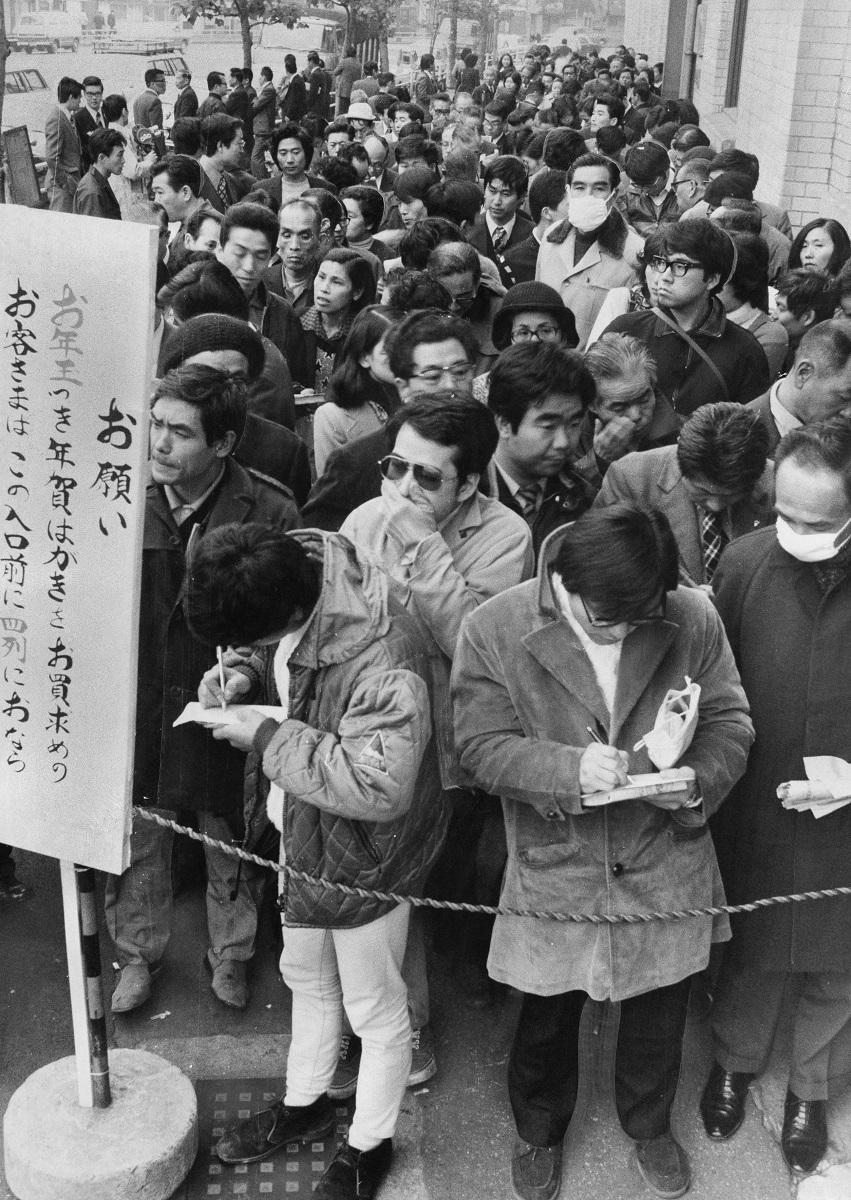 写真・図版 : 年賀はがきを買うために売り出し初日には長蛇の列ができた=1974年11月5日、東京都千代田区の東京中央郵便局前