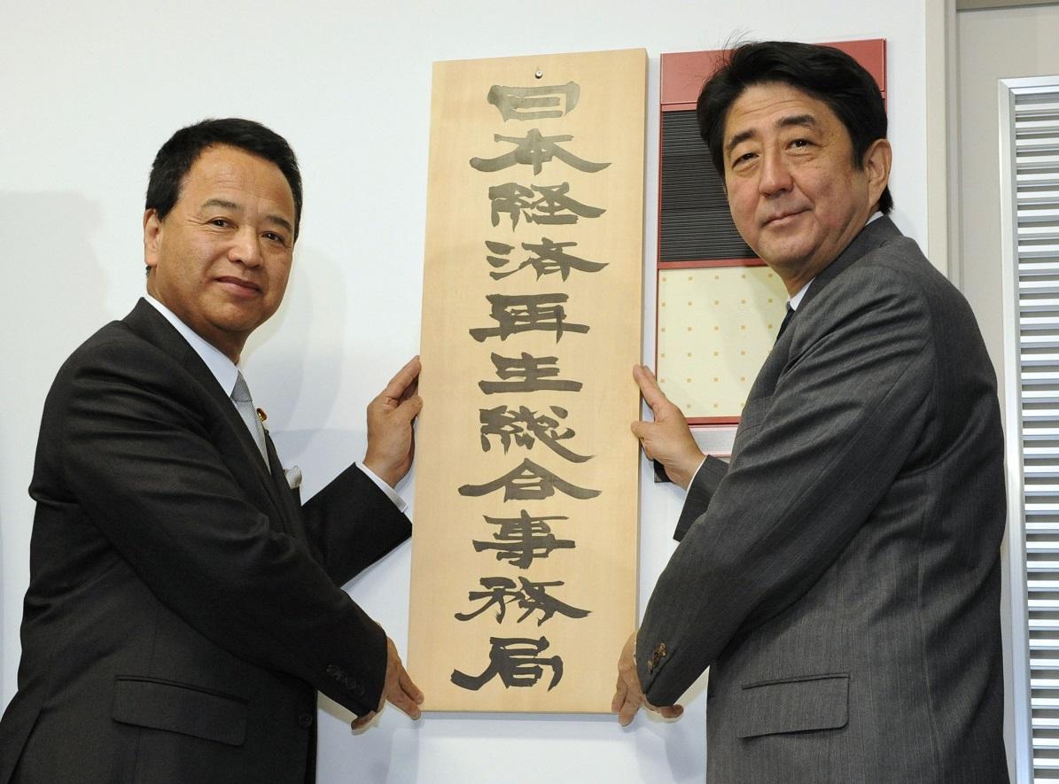 写真・図版 : 「日本経済再生総合事務局」の看板を掛ける安倍首相と甘利経済再生相=2013年1月7日 、内閣府