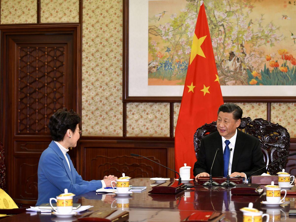 写真・図版 : 中国の習近平国家主席(右)との会談で情勢報告を行う香港の林鄭月娥行政長官=2019年12月16日、北京