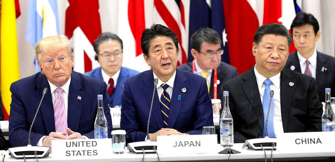 写真・図版 : G20 G20サミットで行われたデジタル経済に関する首脳特別イベントであいさつする安倍晋三首相(中央)。左はトランプ米大統領、右は中国の習近平国家主席=2019年6月28日、大阪市住之江区