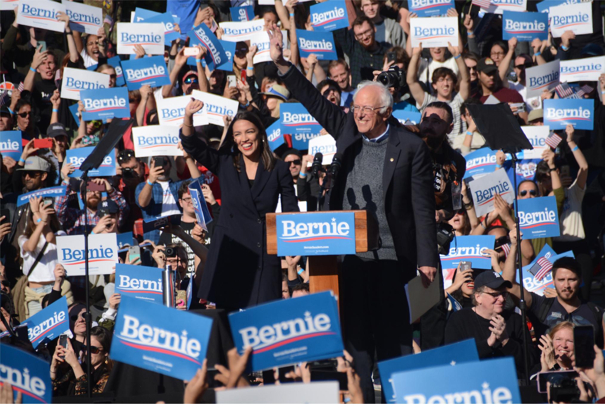写真・図版 :  聴衆に手を振るバーニー・サンダース上院議員(中央右)と、同氏への支持を表明したアレクサンドリア・オカシオコルテス下院議員=2019年10月19日、米ニューヨーク市
