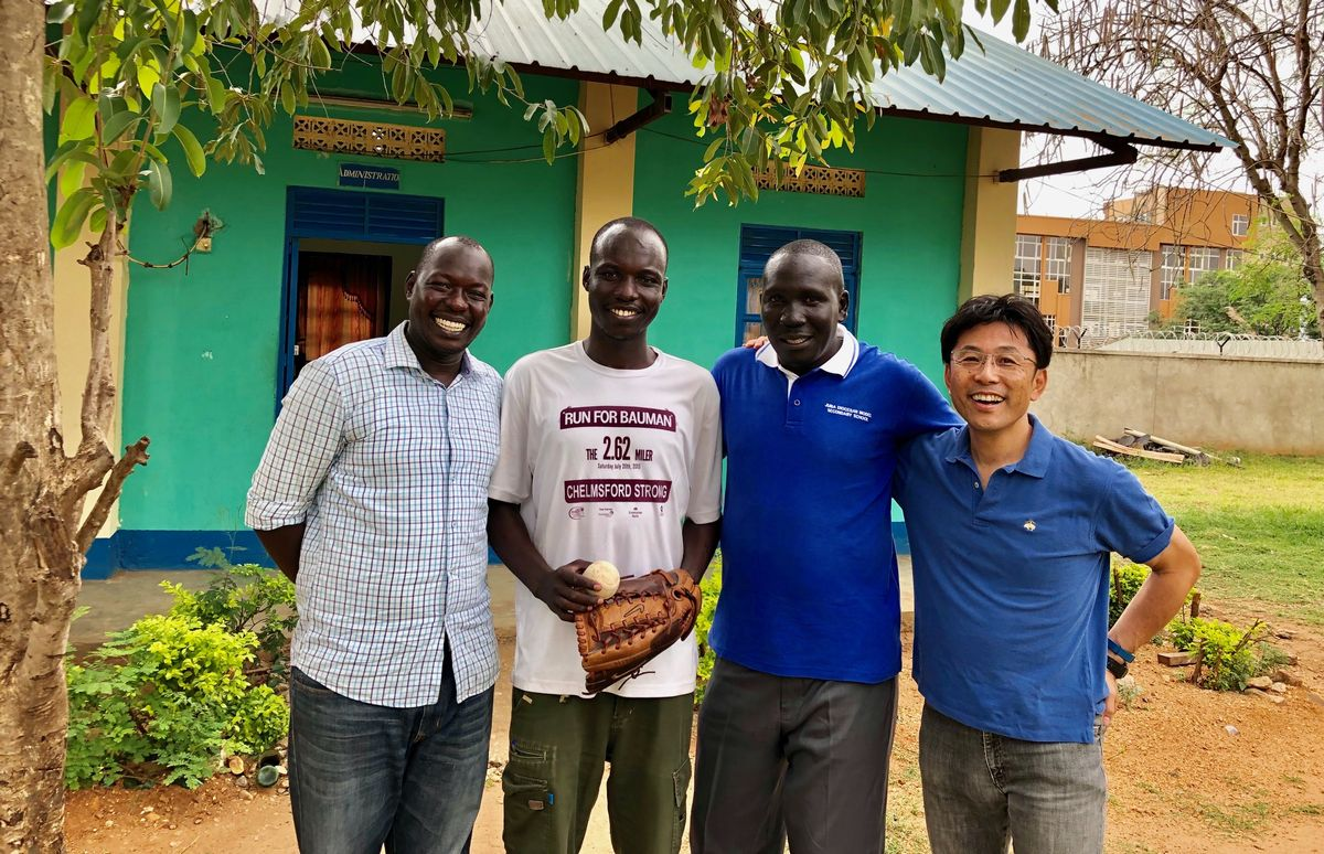 写真・図版 : 校長室の前で、左から、ピーター、ウィリアム、校長先生、筆者。