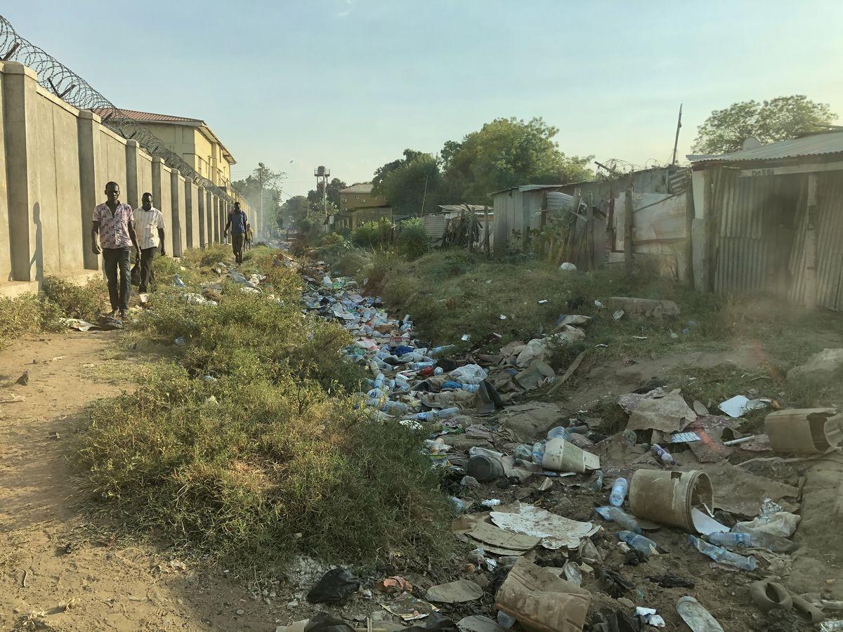 写真・図版 : まるでごみ廃棄場のような風景だが、もともとは人や車が通る公道。雨季に入って川のような状態でごみが浮遊し、、乾季に入って浮遊していたゴミが散逸している様子。