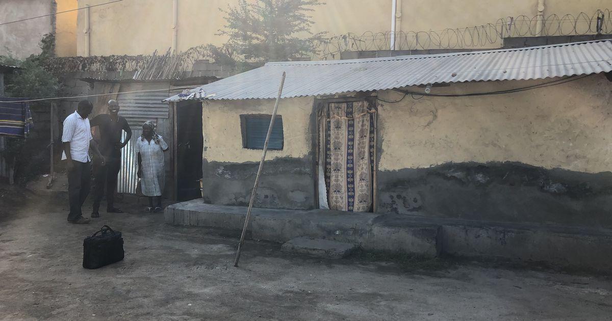 写真・図版 : コンパウンドの中にあるおばあさんの自宅敷地内。右側の家は土塀にトタン屋根。その左に調理場所がある。