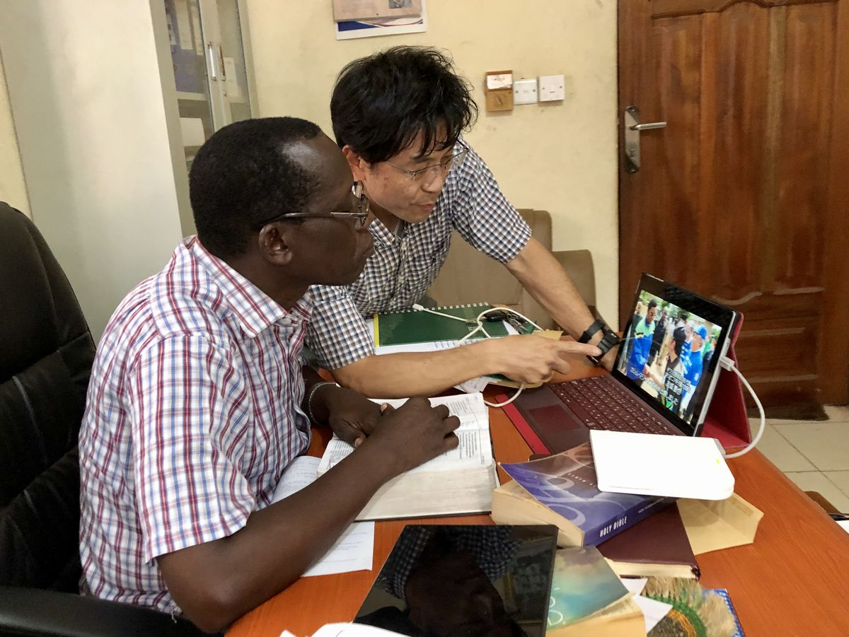写真・図版 : 野球を見たことがないというジャクソン事務局長にタンザニア甲子園の映像を見せる。
