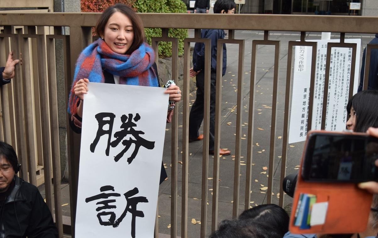 写真・図版 : 「勝訴」の旗を持って判決を報告する伊藤詩織さん=2019年12月18日、東京・霞が関の東京地裁前