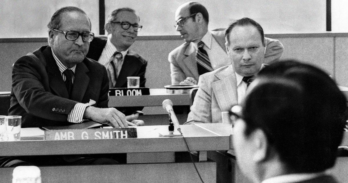 写真・図版 : 使用済み燃料の再処理をめぐって難航した日米核燃料交渉。スミス米国首席代表(左)と向き合うのは、日本の宇野宗佑科学技術庁長官(後ろ姿)=1977年8月29日、東京・外務省