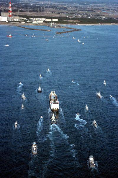 写真・図版 : 警備の船に囲まれて入港する、フランスからの返還プルトニウムを載せた輸送船「あかつき丸」=1993年1月5日、茨城県東海村沖、朝日新聞社ヘリ
