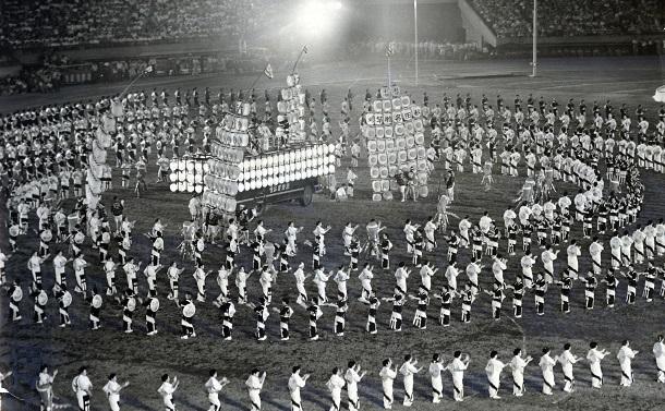 写真・図版 : 「7万人の夕涼み大会」では東京・国立競技場で1500人が「東京音頭」を踊った=1960年8月1日