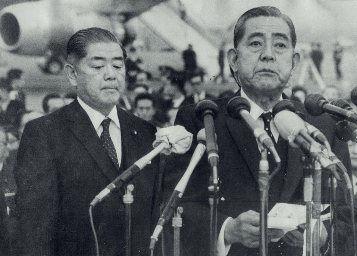 写真・図版 : 1972年に沖縄の施政権を返還することをうたった日米共同声明を発表した日米首脳会談を終え帰国、沖縄返還などについてのステートメントを読み上げる佐藤栄作首相(中央)。左は愛知揆一外相 =1969年11月26日