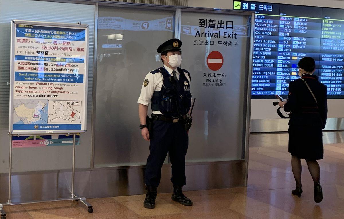 写真・図版 : 羽田空港国際線ターミナルの到着口には注意喚起を知らせるポスターがはられていた=2020年1月31日、岩崎撮影