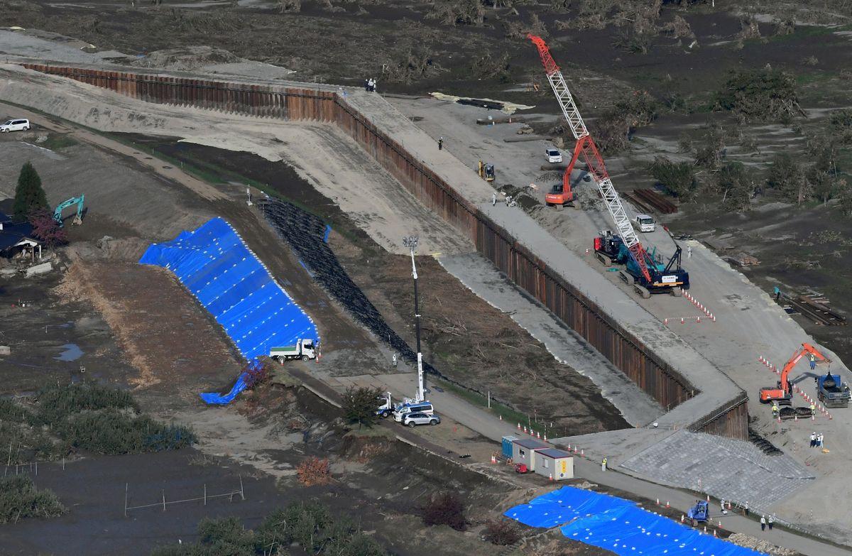 写真・図版 : 決壊した千曲川には、鋼板が打ち込まれ、仮堤防が造られた=2019年10月30日、長野市穂保、朝日新聞社ヘリから
