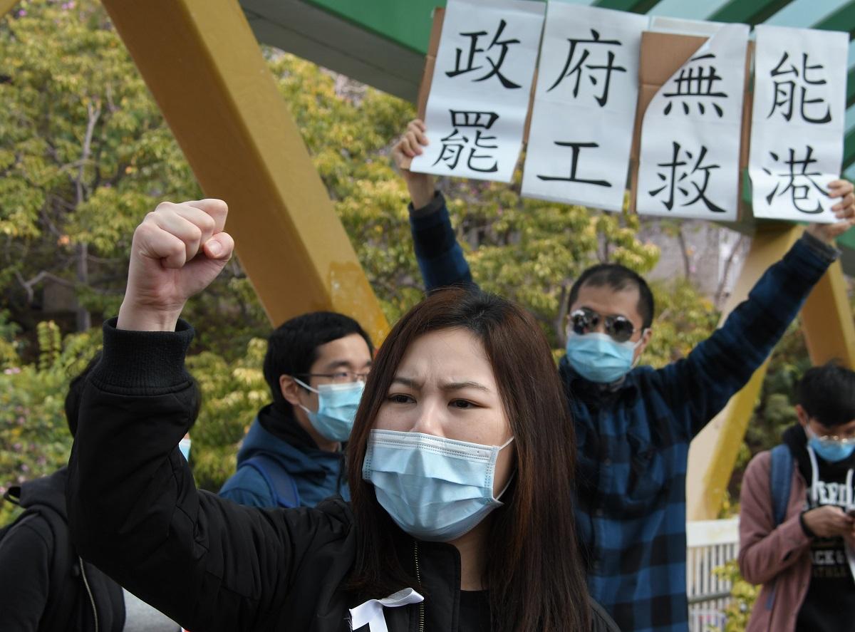 写真・図版 : 医療従事者による抗議デモ。プラカードには「政府が無能なので、ストライキで香港を救え」と書かれている=2020年2月3日、香港島