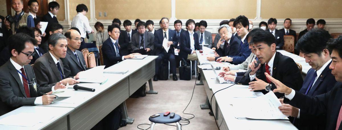 写真・図版 : 「桜を見る会」追及本部のヒアリングに臨む野党議員ら(右側)。左側は内閣府、消費者庁などの担当者ら=2019年12月12日、国会内