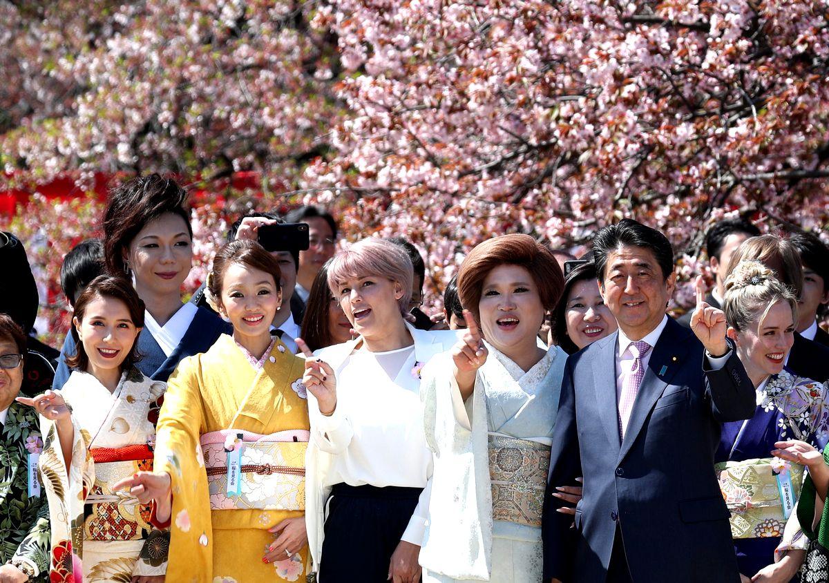 写真・図版 : 安倍晋三首相(手前右から2人目)と記念写真を撮る「桜を見る会」の参加者たち=2019年4月13日、東京都新宿区