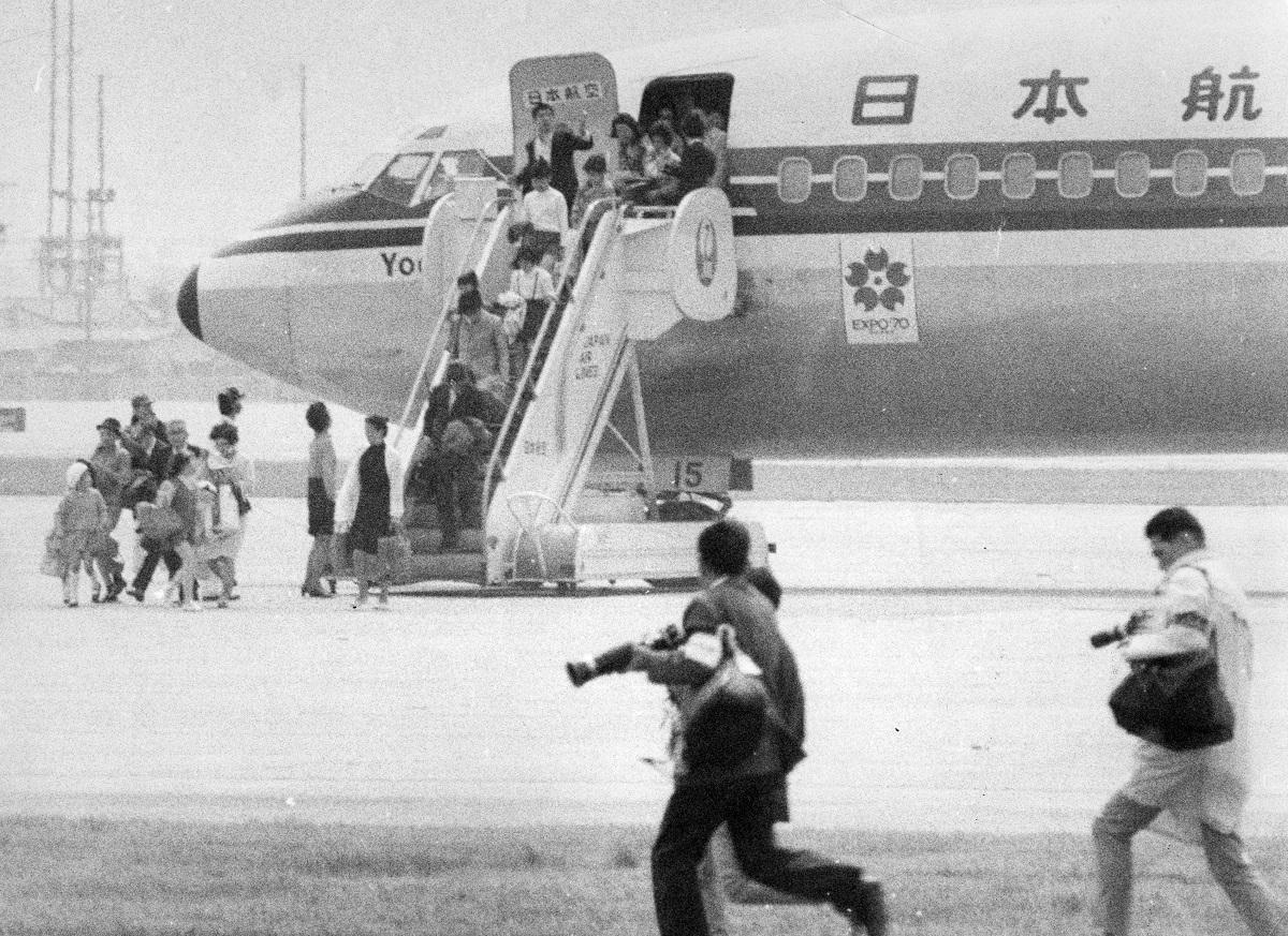 よど号ハイジャック事件で、同機から解放される女性、子ども、老人たち。タラップ最上段に日本刀をもった乗っ取り犯がいる331板付