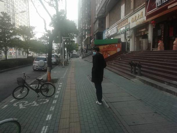 写真・図版 : 中国・湖北省武漢市の街を歩くパキスタン人留学生。ほとんどの店は閉まっているという=2020年2月6日、アクタール・アラムさん撮影