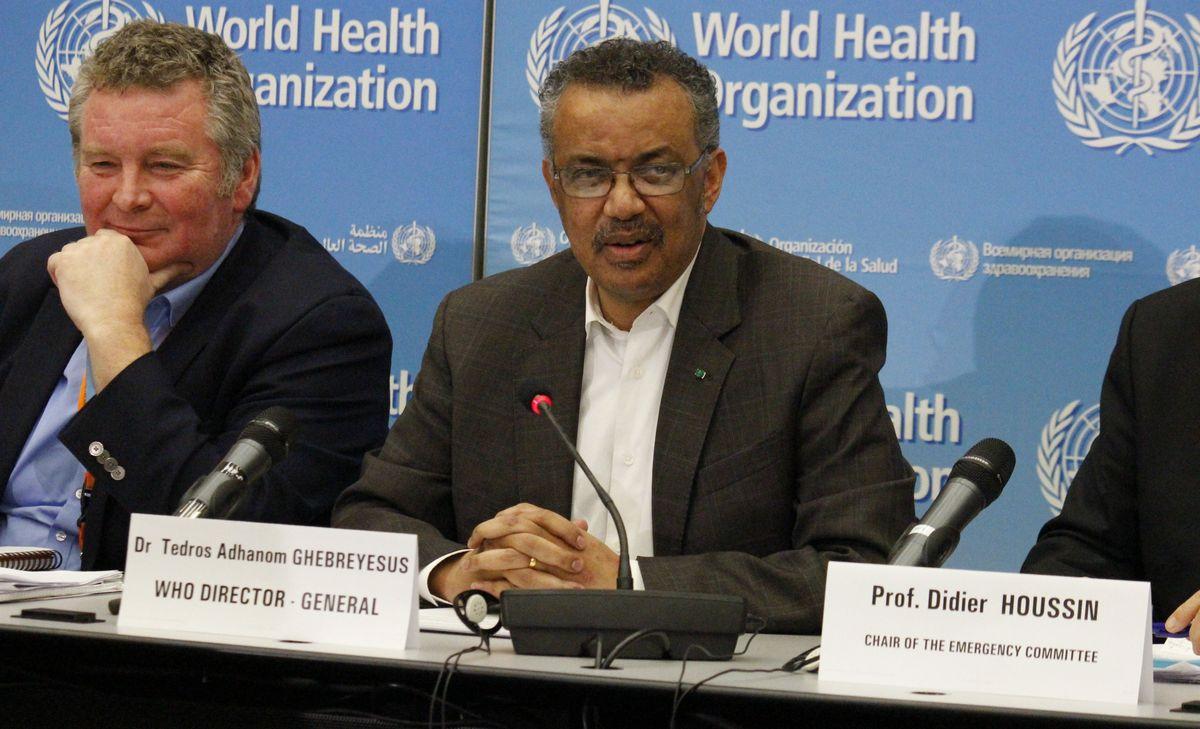 写真・図版 : 新型コロナウイルスについて緊急事態を宣言するWHOのテドロス・アダノム事務局長(中央)=2020年1月30日、ジュネーブ