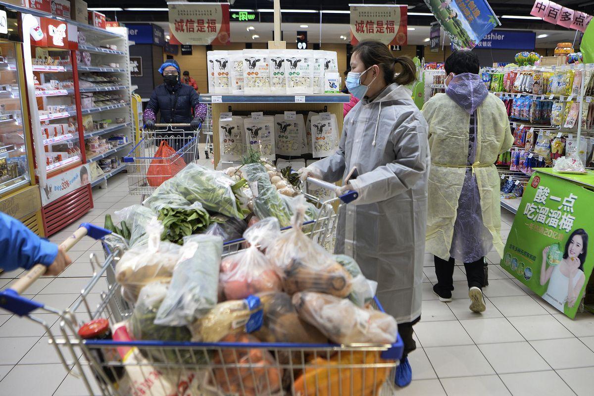写真・図版 : スーパーでの買い物に、レインコートとマスクをして出掛ける人たち=2020年2月10日、中国・武漢(AP)