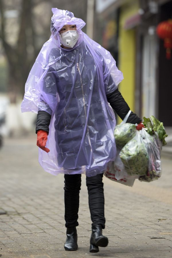 写真・図版 : マスクとレインコートを着て買い物をする女性=2020年2月10日、中国・武漢(AP)