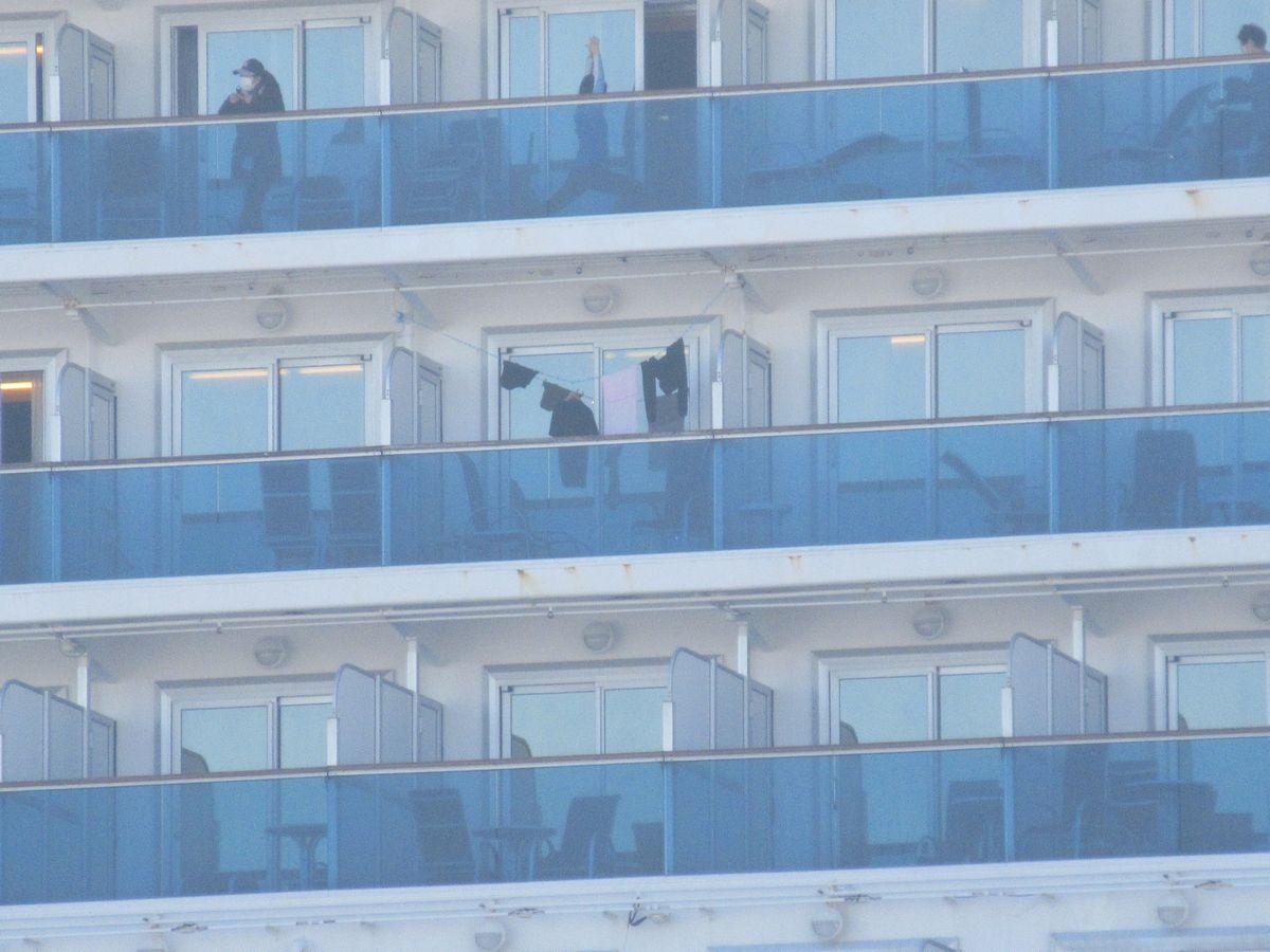 写真・図版 : 横浜港の大黒ふ頭に停泊するダイヤモンド・プリンセス号。バルコニーのある船室の乗客は、外に出てストレッチをする人もいた=2020年2月13日、岩崎撮影