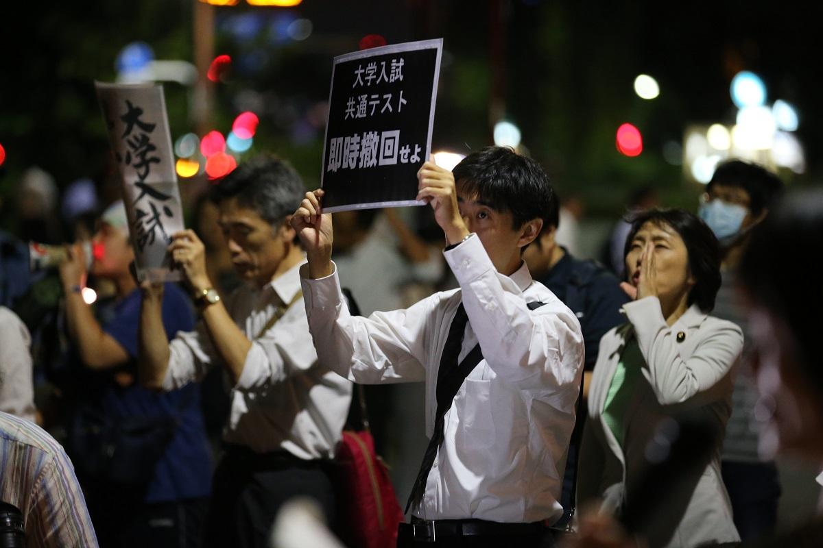 写真・図版 : 文部科学省前でプラカードを掲げ、大学入試改革の中止を求める人々=2019年9月13日、東京・霞が関