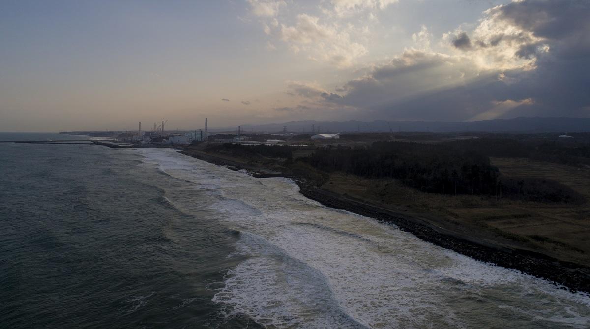 写真・図版 : 双葉町の海岸。奥に福島第一原発が見える=2018年3月11日