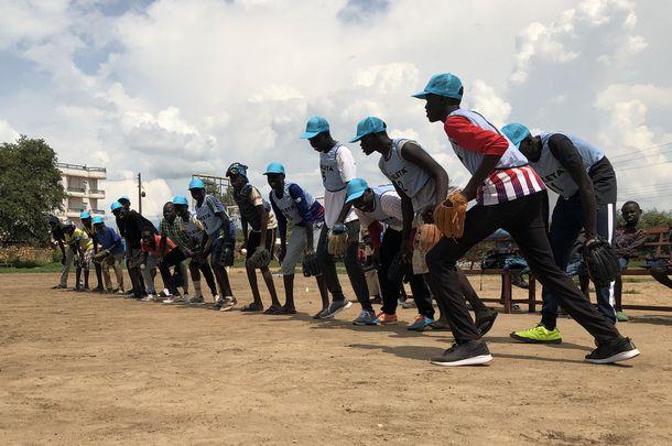 写真・図版 : ベンチ前整列し、「いくぞ!」「おーっ!」と元気よく飛び出す南スーダンナイン