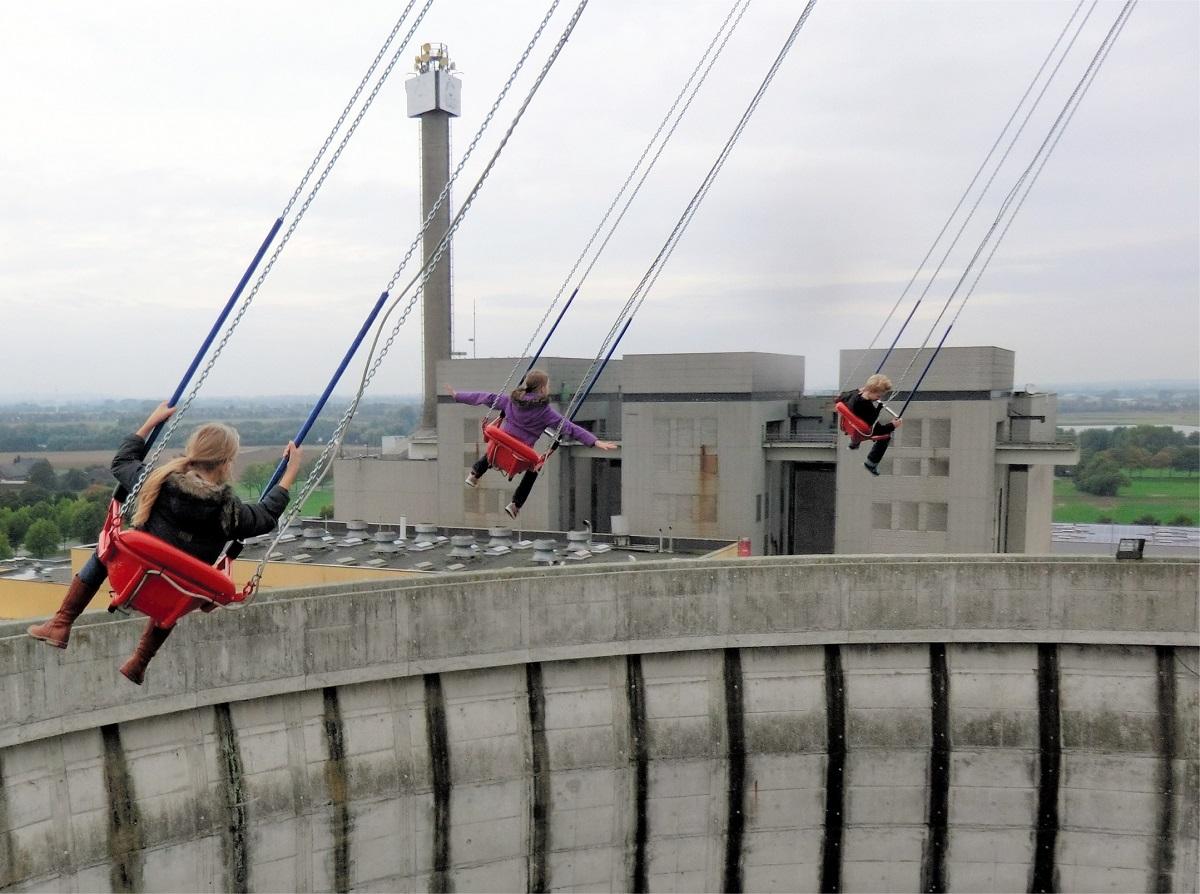 写真・図版 : 高速増殖炉の冷却塔だった建物の中にある「空中ブランコ」は人気のアトラクション。後ろの建物の中にあった原子炉は使われないまま解体された=2013年、独カルカー