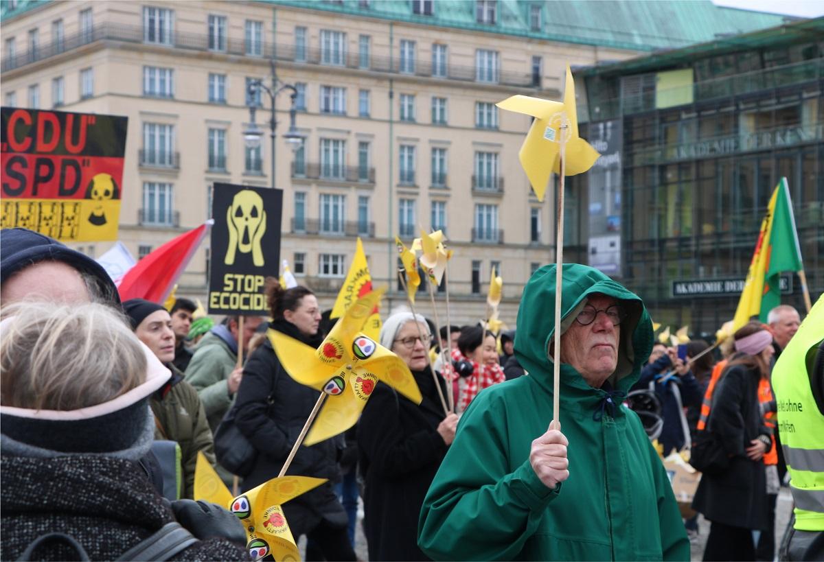 写真・図版 :    風力発電をイメージする「かざぐるま」を持って街を歩く反原発デモの参加者=2019年、ベルリン