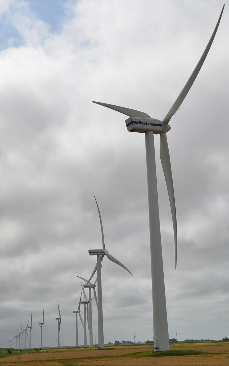 写真・図版 : 強風を受けて回る発電用の風車群。ドイツ政府はこの地域の電気を南部の産業地帯に送る必要があるとした=2013年、ドイツ北部北フリースラント郡