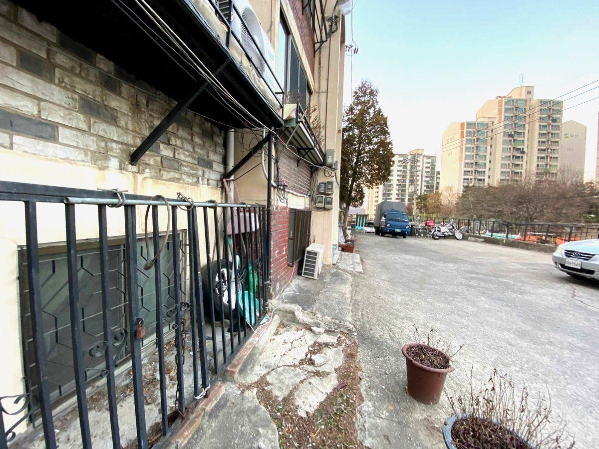 写真・図版 : 高層マンション群の近くにある半地下の住居。道路と同じ位置に窓がある=2020年2月10日、ソウル