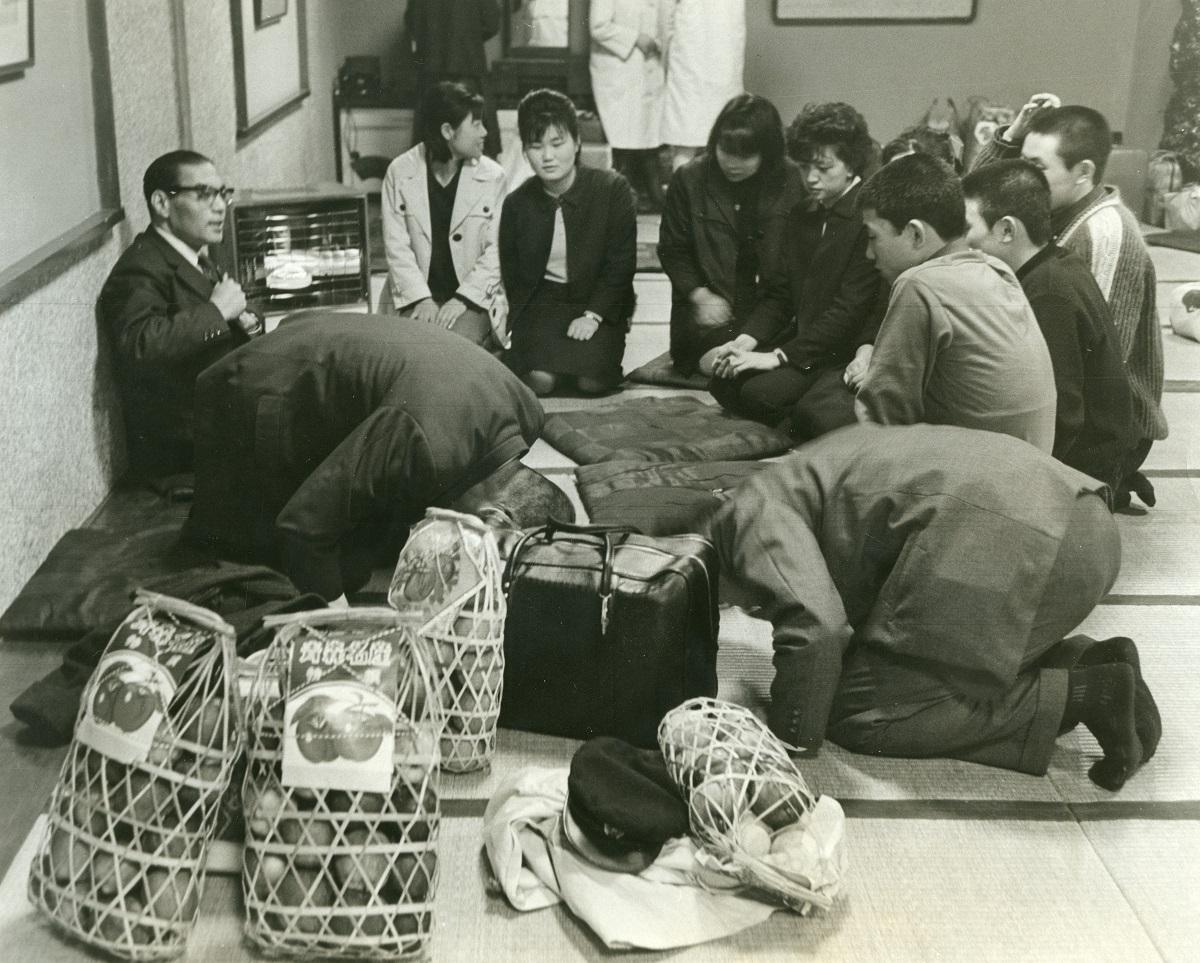 写真・図版 : 青森から上京したばかりの集団就職者たち。右側で「どうぞよろしく」と頭を下げるのは引率の先生=1965年3月6日、東京・上野駅前の旅館