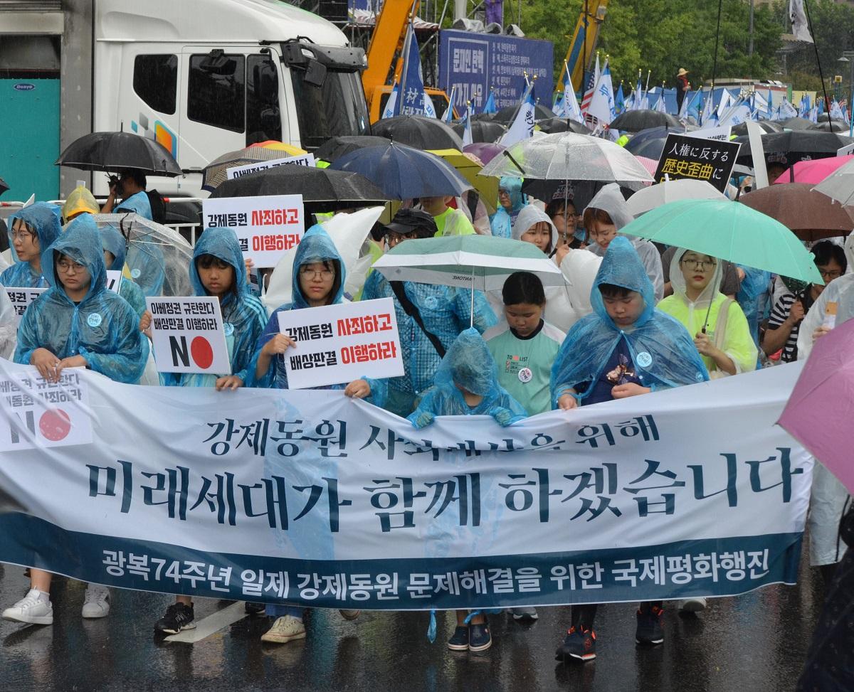 写真・図版 : 「強制動員を謝罪し 賠償判決を理解しろ」などと書かれたプラカードを持ち、ソウルの日本大使館に向かってデモ行進する元徴用工の支援者ら=2019年8月15日