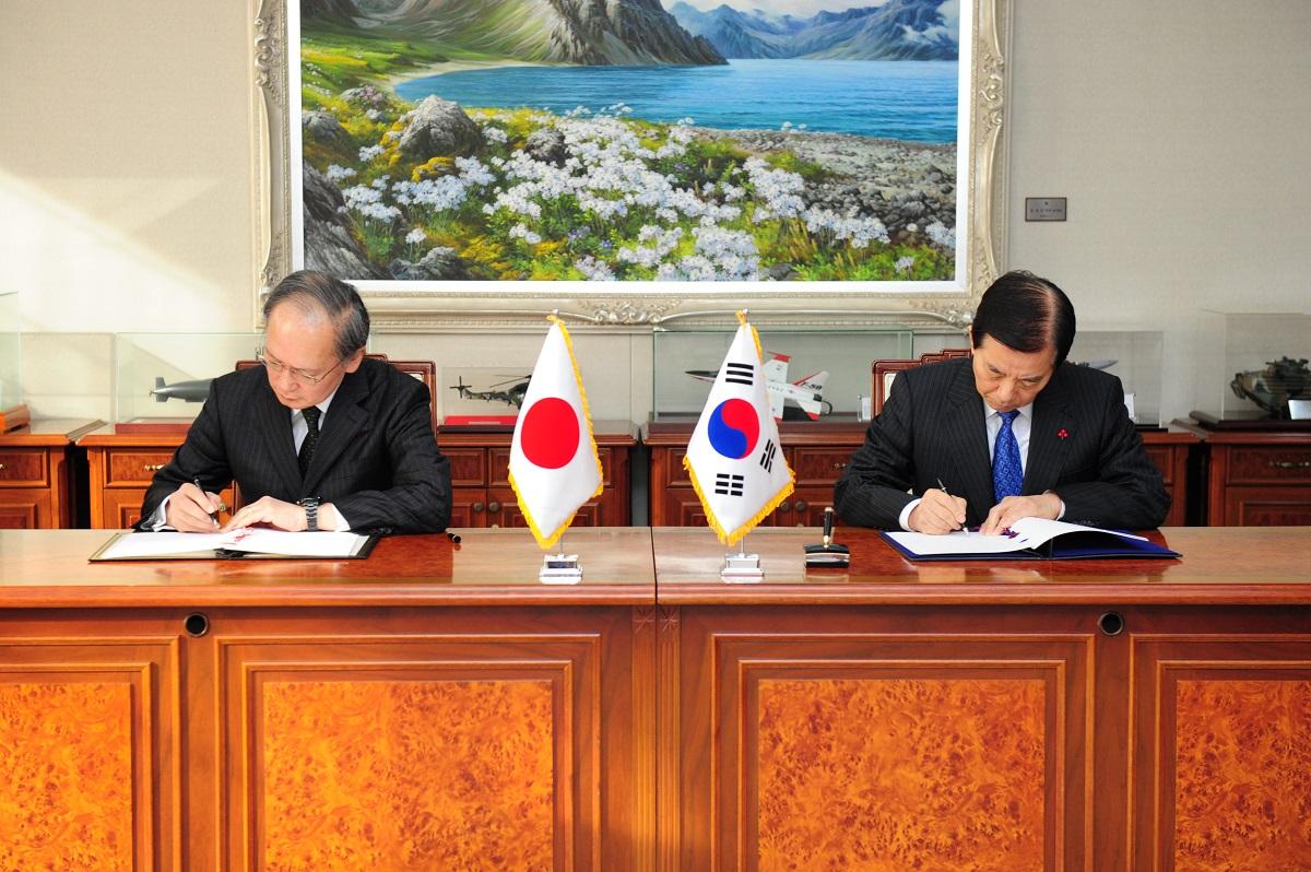 写真・図版 : 2016年11月、ソウルで日韓GSOMIAに署名する、長嶺安政駐韓大使(左)と韓民求・韓国国防相(いずれも当時)=韓国国防省提供