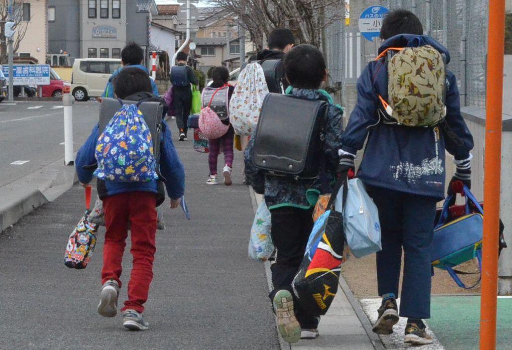 写真・図版 : 来月2日からの休校が決まった鶴岡市で、置いてあった教材など多くの荷物を抱えて下校する児童たち=2020年2月28日、山形県鶴岡市